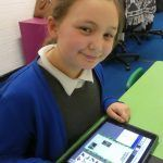 A child smiles as she writes a geography fact file on ainforest Habitats on a tablet using Purple Mash