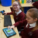 2 children smile to camera as they work together to design a 3D game.