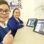 Two children smile to camera after completing a coding challenge in 2Code, the coding tool in Purple Mash