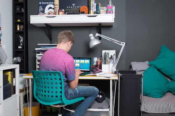 Student completing homework on desk in bedroom