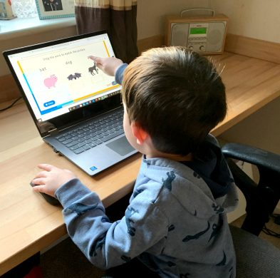 A young child using an interactive spelling game on Classroom Secrets Kids
